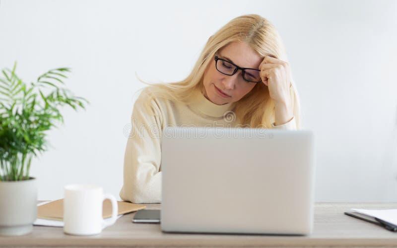 Mulher de neg?cios madura sobrecarregado Suffering From Headache no escrit?rio imagem de stock royalty free