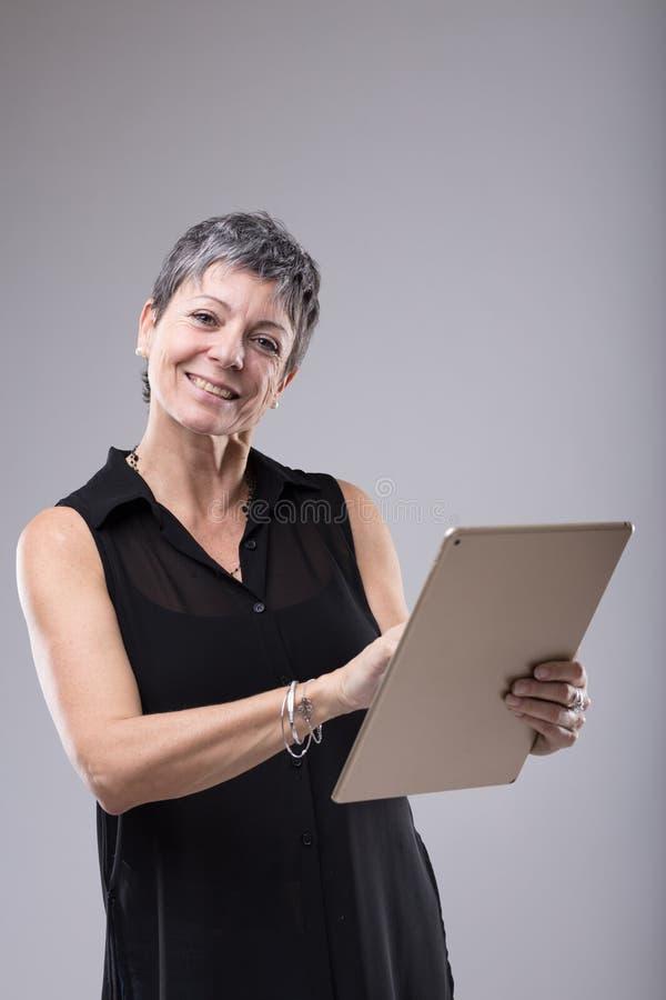 Mulher de negócios de meia idade atrativa que usa a tabuleta fotografia de stock royalty free