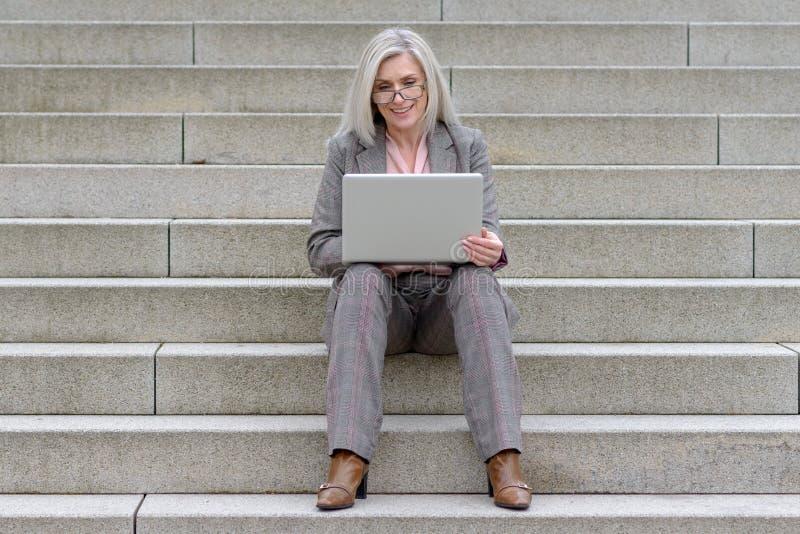 Mulher de negócios de meia idade que usa seu portátil na cidade imagens de stock