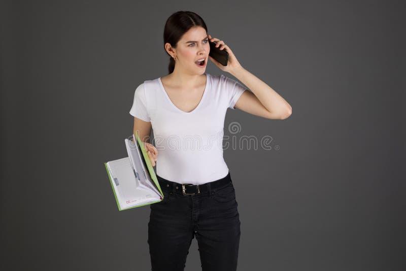 Mulher de negócios moreno agressiva irritada no t-shirt branco imagens de stock royalty free