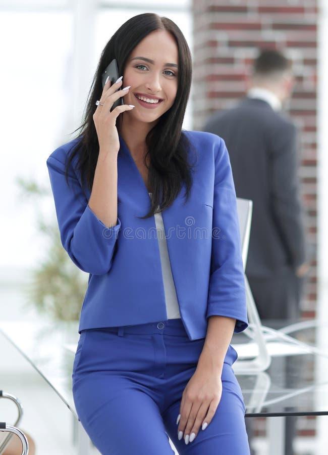 Mulher de negócios moreno atrativa que fala no telefone celular imagem de stock royalty free