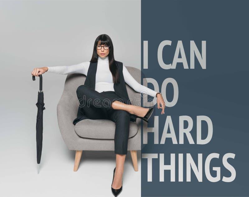 a mulher de negócios moreno bonita que senta-se na poltrona com o guarda-chuva no cinza com você pode fazer imagens de stock