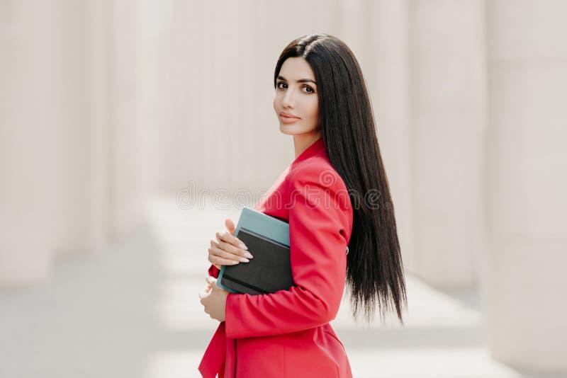 A mulher de negócios moreno séria com composição, tratamento de mãos, veste o revestimento vermelho, leva o diário e o bloco de n imagem de stock