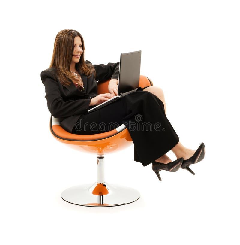 Mulher de negócios na cadeira com portátil fotografia de stock royalty free