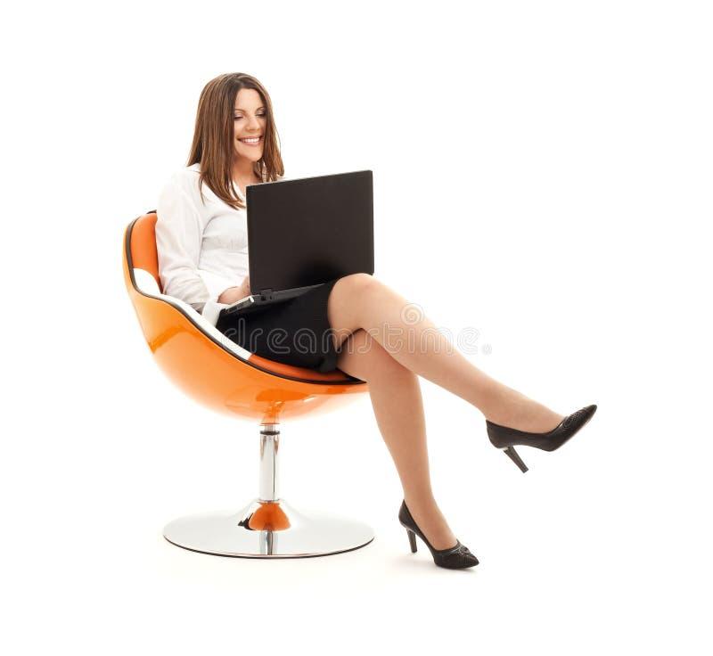 Mulher de negócios na cadeira com portátil imagem de stock