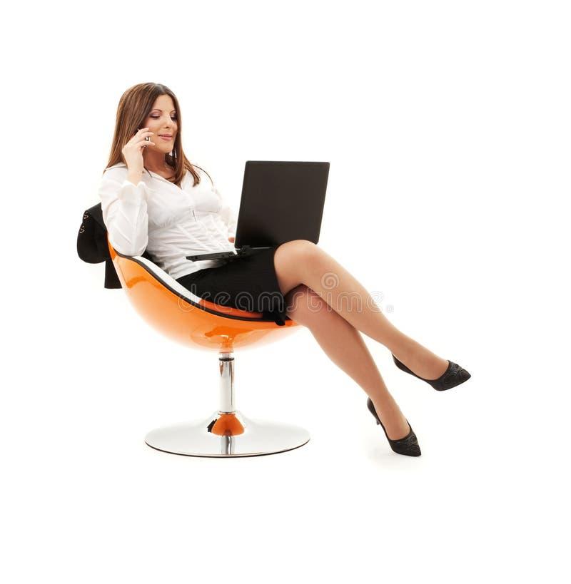 Mulher de negócios na cadeira com portátil e telefone foto de stock