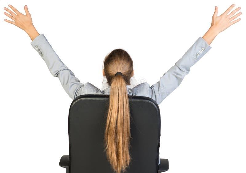 Mulher de negócios na cadeira do escritório que estica seus braços imagem de stock royalty free