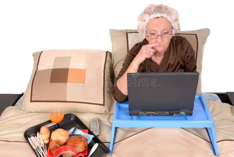 Mulher de negócios na cama, trabalhando fotografia de stock