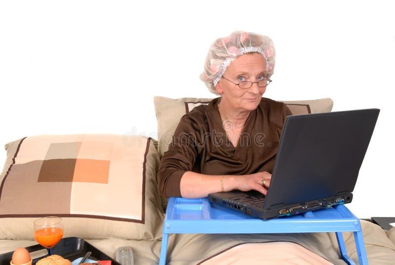 Mulher de negócios na cama, trabalhando foto de stock royalty free