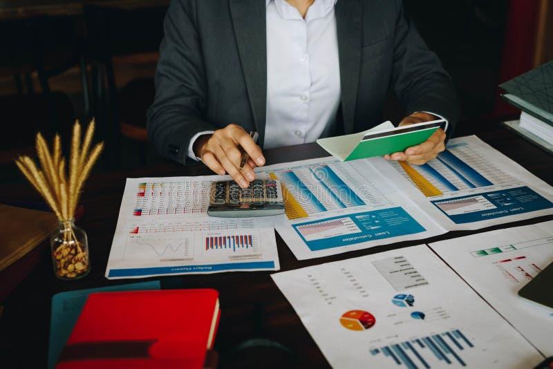 Mulher de negócios na mesa no escritório usando a calculadora para calcular o sa fotos de stock royalty free