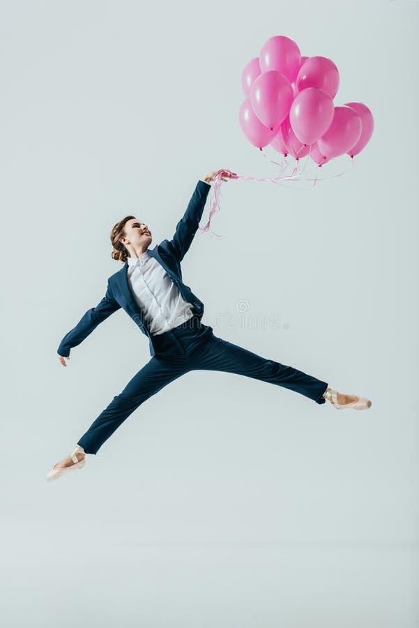 mulher de negócios nas sapatas do terno e de bailado que saltam com balões cor-de-rosa fotografia de stock royalty free