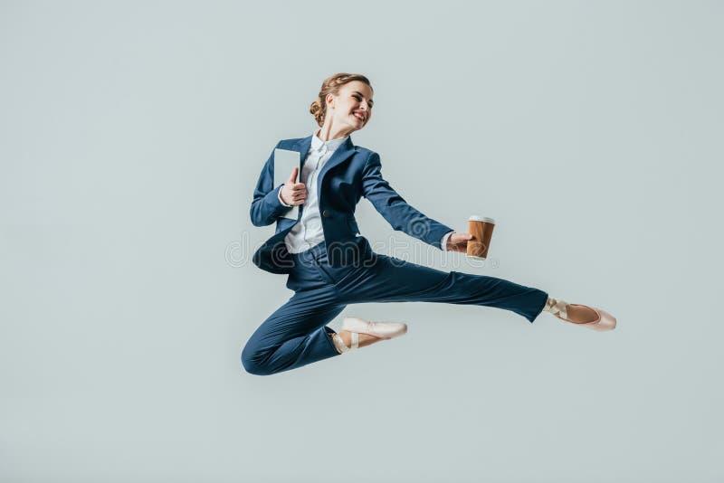 mulher de negócios nas sapatas do terno e de bailado que saltam com café e a tabuleta digital foto de stock royalty free