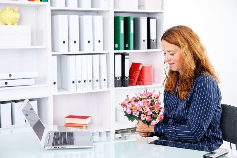 Mulher de negócios no escritório com o ramalhete grande das flores fotografia de stock royalty free