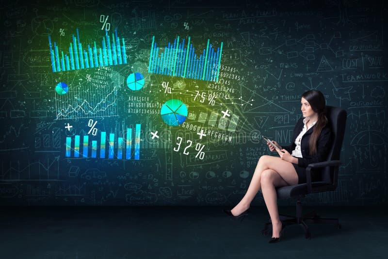Mulher de negócios no escritório com tabuleta à disposição e alto - gráfico da tecnologia fotos de stock royalty free