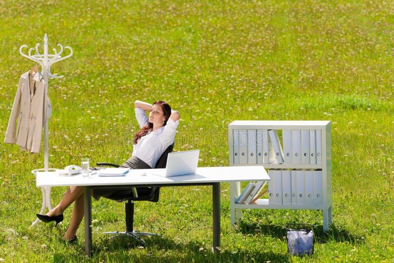A mulher de negócios no prado ensolarado relaxa o escritório da natureza fotos de stock