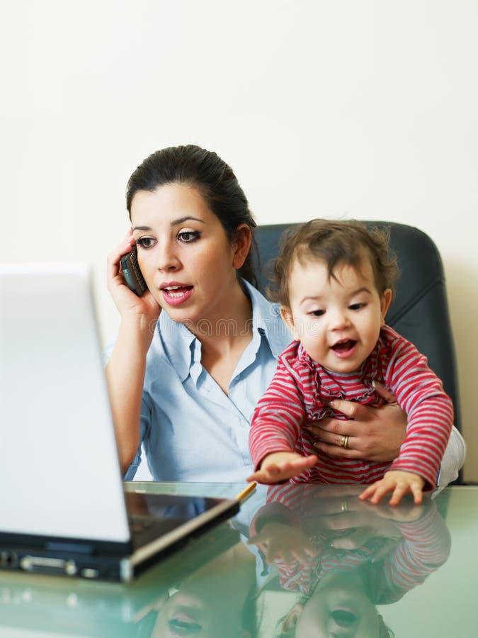 Mulher de negócios no telefone, prendendo a filha foto de stock royalty free