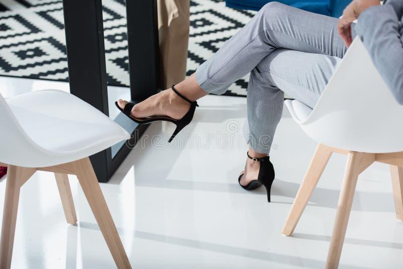 A mulher de negócios no terno e na elevação colocou saltos as sapatas que sentam-se na cadeira no escritório imagens de stock