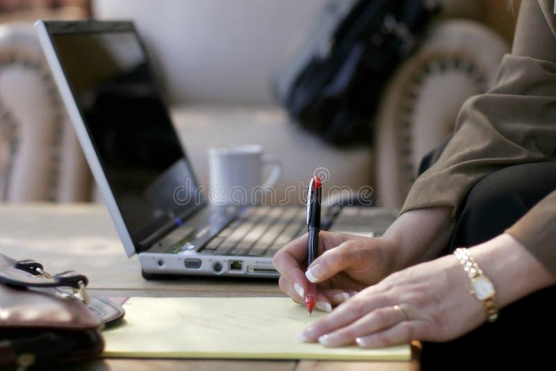 Mulher de negócios, notas, portátil, & vestíbulo do hotel fotografia de stock