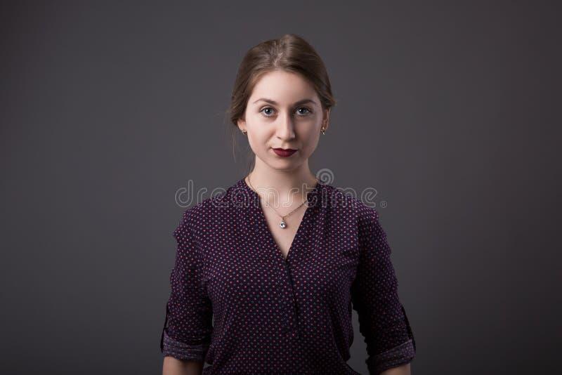 Mulher de negócios nova à moda com uma expressão amigável que olha diretamente na câmera, close up de sua cara em um cinza imagem de stock
