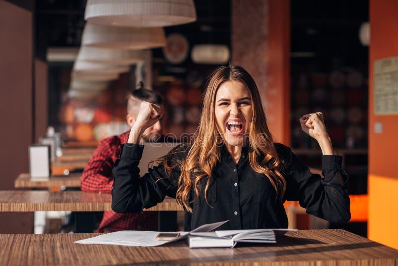 A mulher de negócios nova alegre que mantém os braços levanta a comemoração do sucesso no café fotografia de stock royalty free