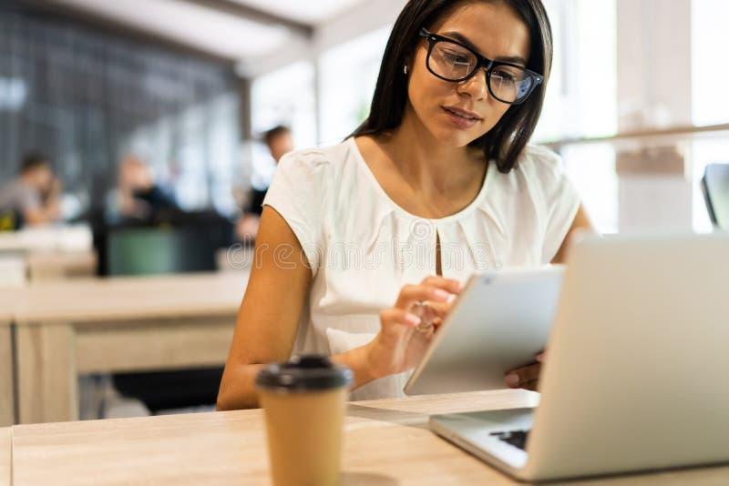 Mulher de negócios nova alegre que usa o PC da tabuleta no escritório imagem de stock