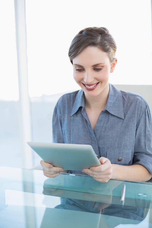 Mulher de negócios nova alegre que usa sua tabuleta que senta-se em sua mesa fotografia de stock royalty free