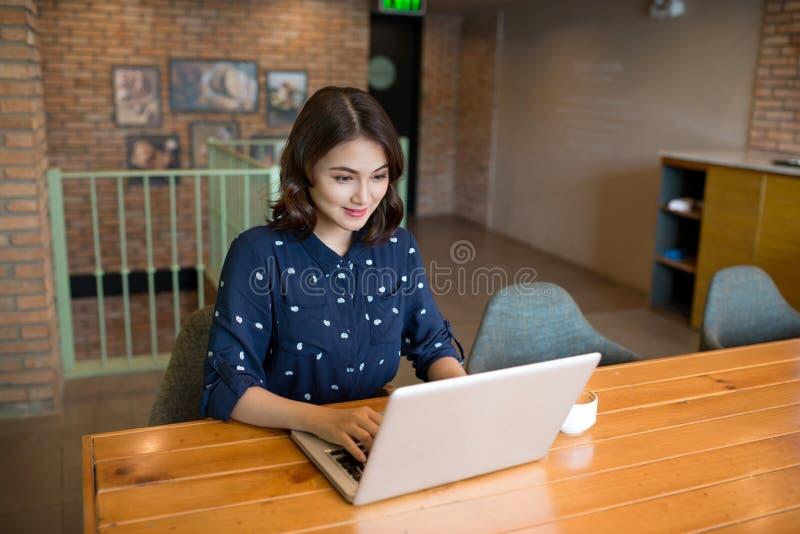 Mulher de negócios nova asiática bonito bonita no café, usando o lapt imagem de stock