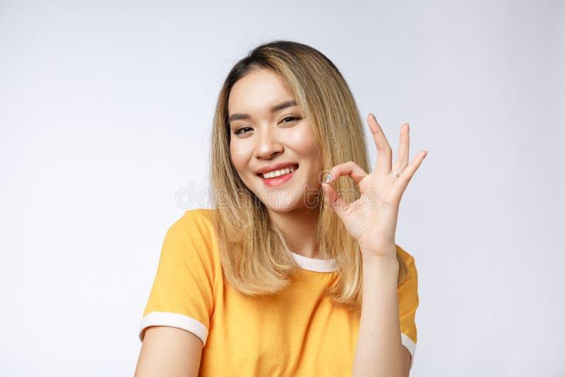 Mulher de negócios nova asiática com gesto aprovado do sinal fotografia de stock