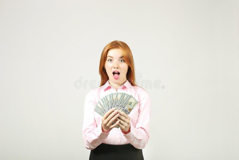 A mulher de negócios nova atrativa que levanta com grupo de USD desconta dentro as mãos que mostram emoções positivas e a express fotos de stock