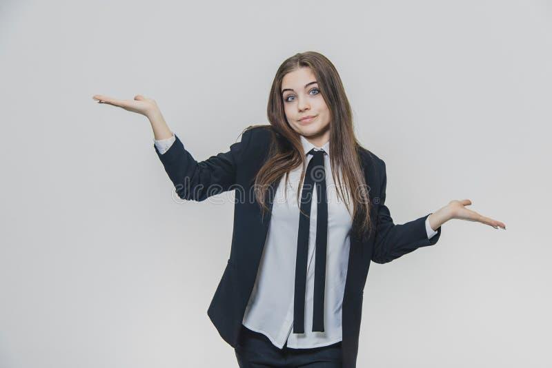 A mulher de negócios nova, atrativa shrugging seus ombros e threwing suas ambas as mãos acima, olhando em linha reta no foto de stock