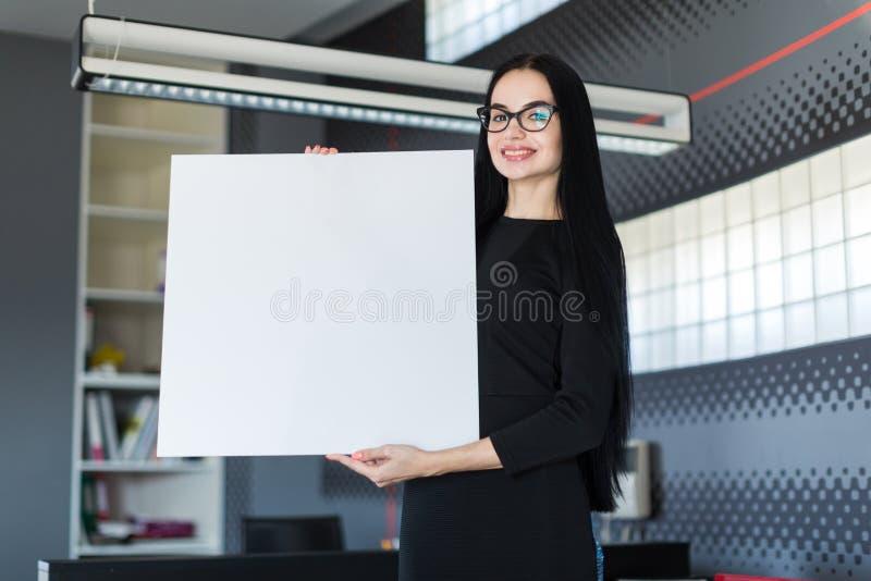 A mulher de negócios nova bonita no vestido preto e os vidros guardam o cartaz vazio fotografia de stock royalty free