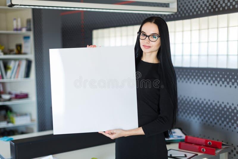 A mulher de negócios nova bonita no vestido preto e os vidros guardam o cartaz vazio fotos de stock