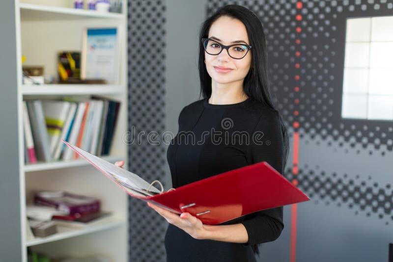 A mulher de negócios nova bonita no vestido preto e os vidros guardam o dobrador de papel fotografia de stock