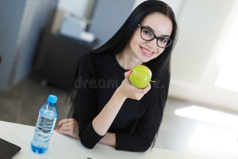 A mulher de negócios nova bonita no vestido preto e os vidros sentam-se na tabela no escritório e guardam-se a maçã verde fotos de stock royalty free