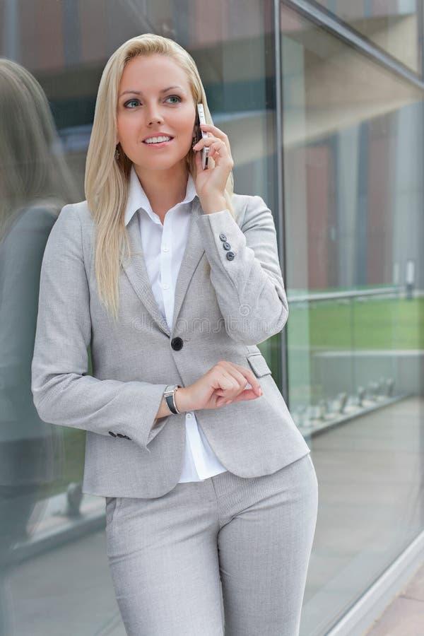 Mulher de negócios nova bonita que conversa no telefone celular ao inclinar-se na parede de vidro fotografia de stock