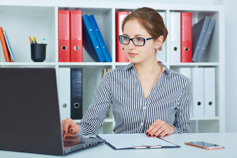 Mulher de negócios nova bonita que trabalha em um portátil no escritório imagens de stock royalty free