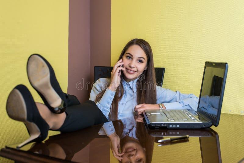 Mulher de negócios nova bonito que senta-se em uma cadeira com seus pés na tabela no escritório É de sorriso e de fala no telefon foto de stock