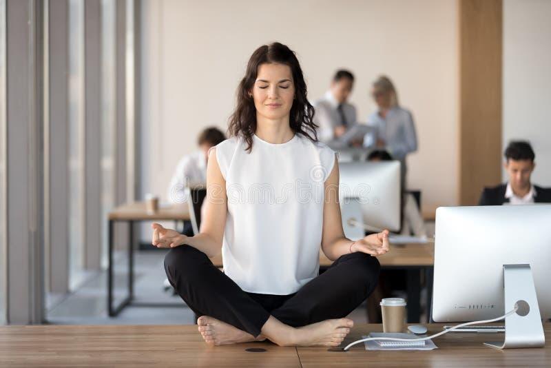 Mulher de negócios nova calma que faz o exercício da ioga na mesa do trabalho imagens de stock royalty free