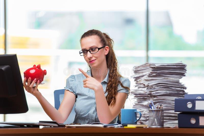 A mulher de negócios nova com o mealheiro no escritório fotos de stock royalty free