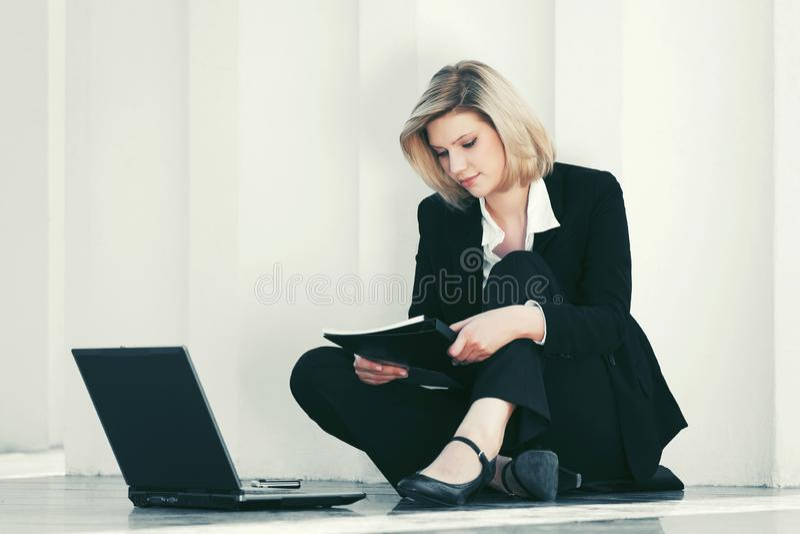 Mulher de negócios nova com o portátil que senta-se na parede imagens de stock