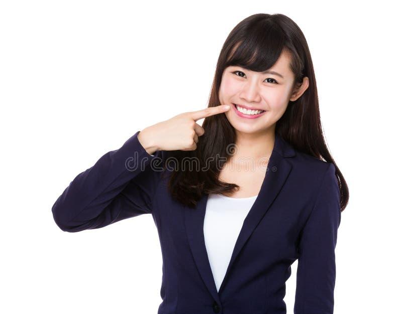 Mulher de negócios nova com ponto do dedo a seus dentes imagens de stock royalty free