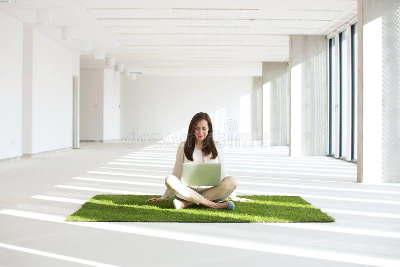 Mulher de negócios nova com portátil ao sentar-se no tapete da grama no escritório vazio imagens de stock