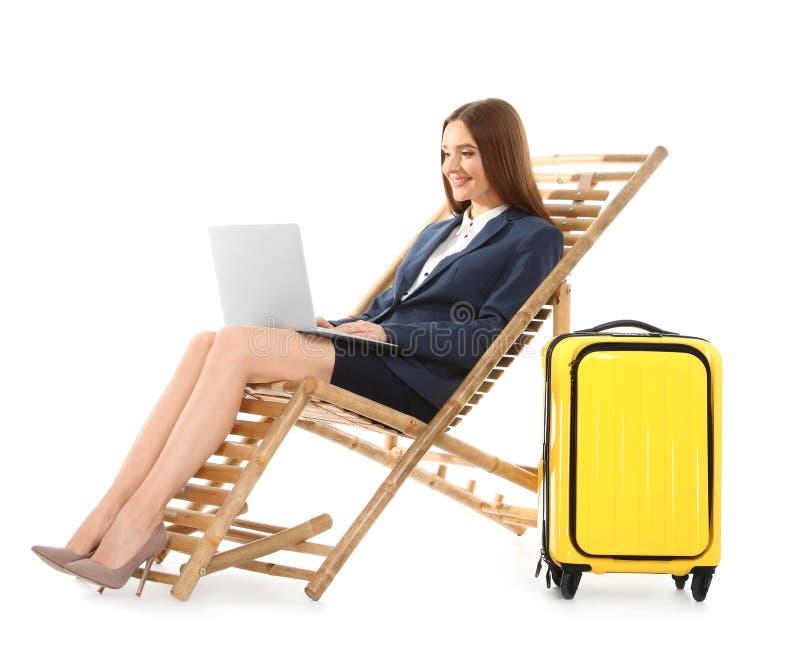 Mulher de negócios nova com portátil e mala de viagem no vadio do sol contra o fundo branco E imagens de stock royalty free