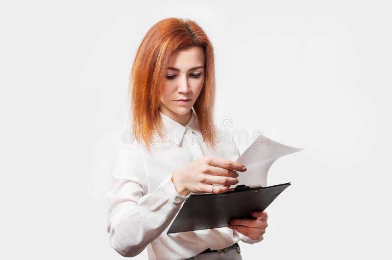 Mulher de negócios nova com a prancheta contra o fundo branco fotos de stock
