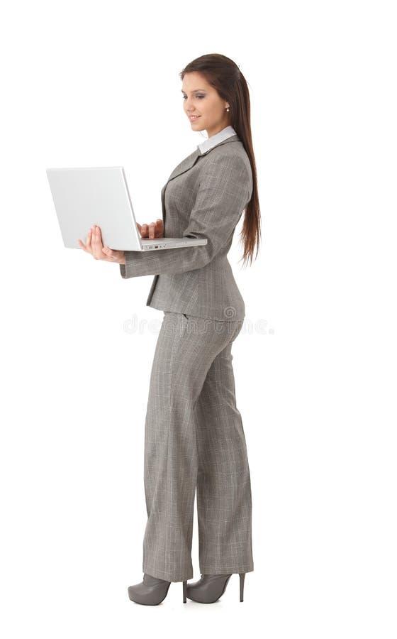 Mulher de negócios nova com sorriso do portátil foto de stock royalty free