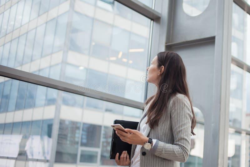 Mulher de negócios nova com vidros e um telefone em suas mãos No escritório ou no centro de negócios fotografia de stock royalty free