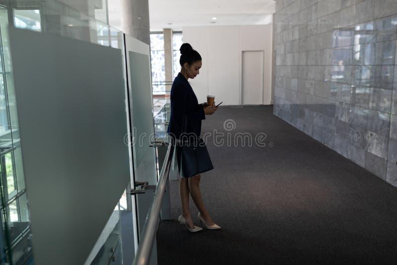 Mulher de negócios nova da misturado-raça com copo de café usando o telefone celular no escritório imagem de stock