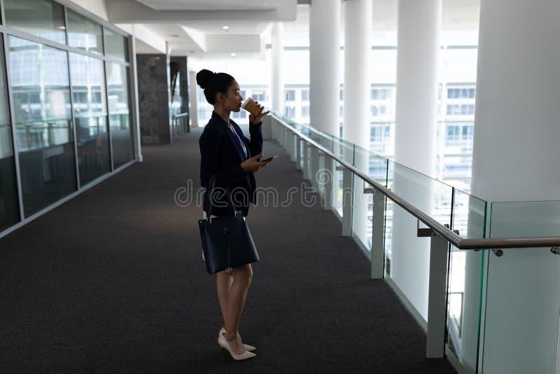 Mulher de negócios nova da misturado-raça que come o café ao usar o telefone celular no escritório foto de stock