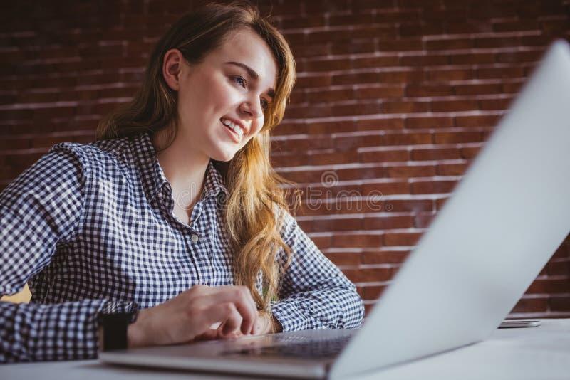 Mulher de negócios nova de sorriso do moderno que usa seu computador imagens de stock royalty free