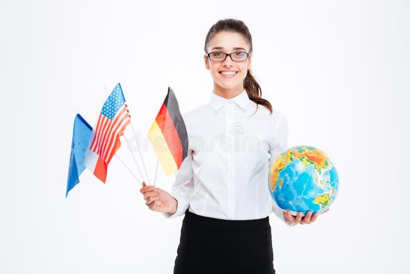 Mulher de negócios nova de sorriso que guarda bandeiras dos países e do globo fotografia de stock royalty free